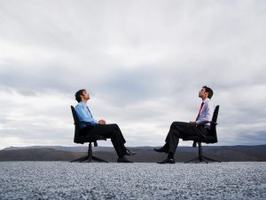 Two men sitting in office chairs outdoors facing each other