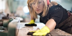 Female craftperson with protective equipment working with planks in workshop