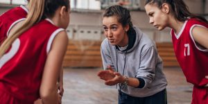 Female coach standing with basketball team on basketball cour