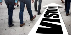 """Businessman(s) follows a right of way arrow that reads """"Vision"""""""