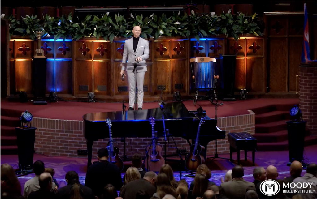 Screenshot from Moody Bible Institute of a television screen depicting a man on stage leading service for a large audience.