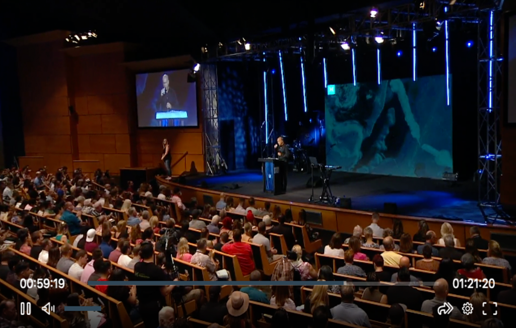 Screenshot of video broadcast from Harvest Ministry depicting a large audience enjoying a religious service.
