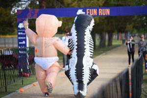 Two people running at a previous 4K 4Charity Fun Run. One is wearing a Giant Babt costume and the other a T-Rex costume.
