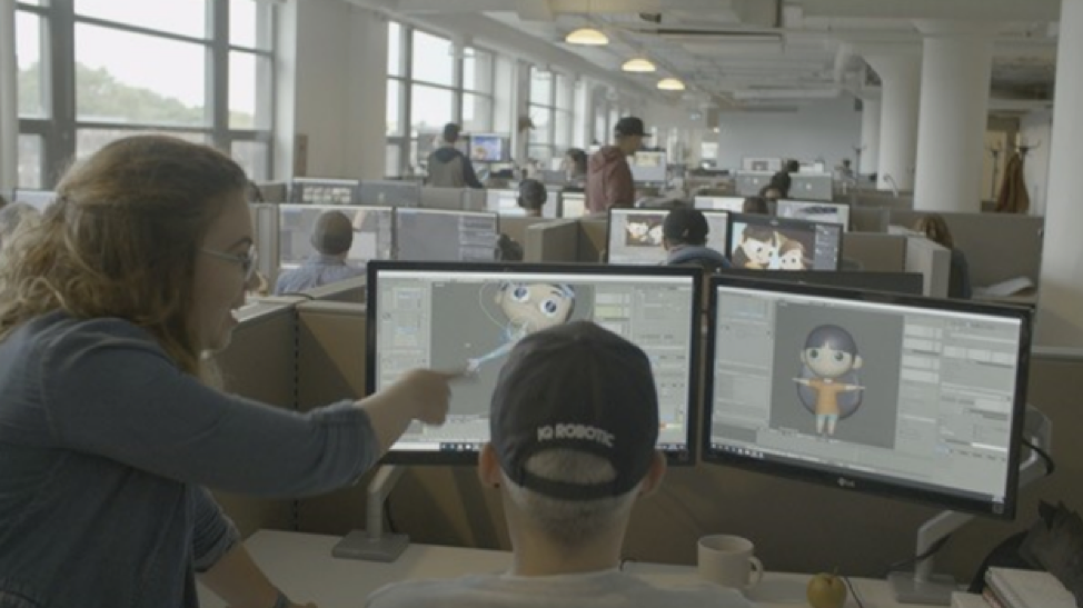 Employees looking at a computer screen with graphics