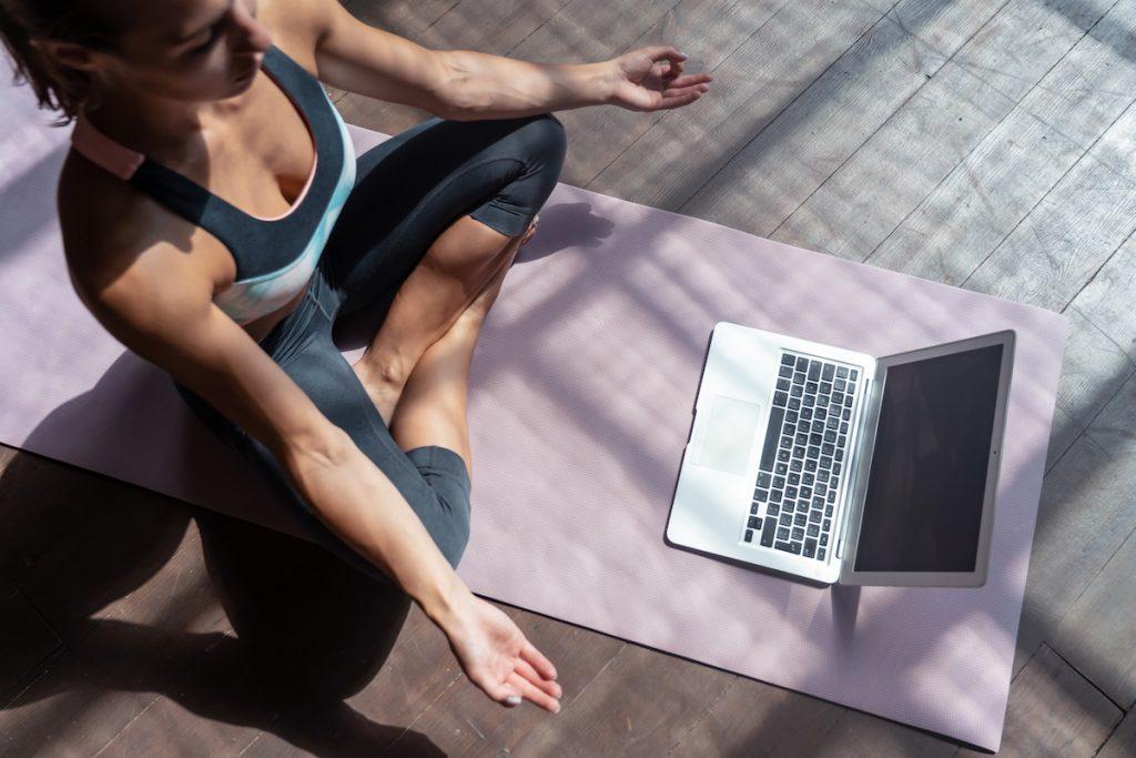 Girl doing yoga using an online platform