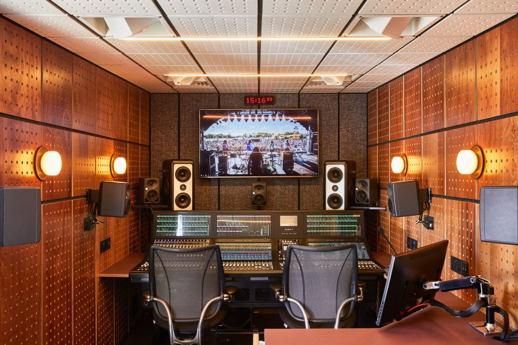 Inside of the Spiritland production truck. On the far wall is a monitor, digital clock, multiple speakers and the soundboard. The sides of the truck are pegboard.